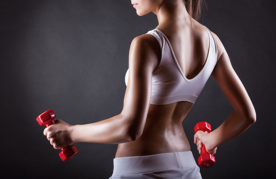 Fitness woman carrying dumbbells